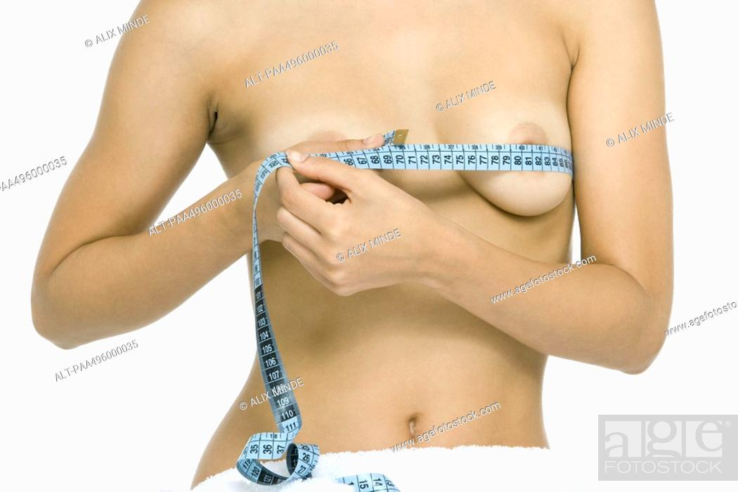 Stock Photo: Nude woman wrapping measuring tape around breasts, cropped view.