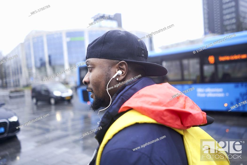 Stock Photo: African man listening to music or podcast on the go, next to bus, in Leeuwarden, Friesland, Netherlands, Europe.