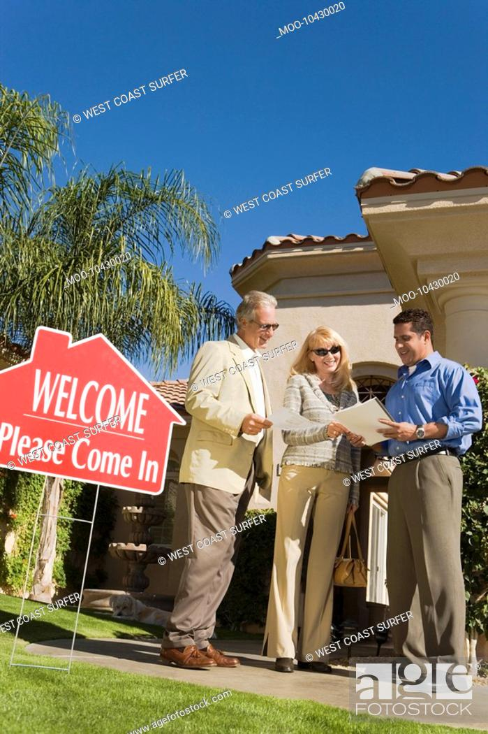 Stock Photo: Couple with estate agent low angle view.
