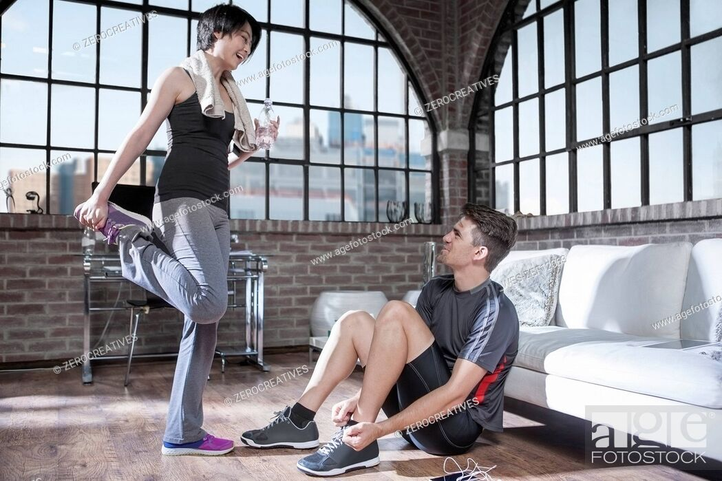 Stock Photo: Young man and woman preparing in exercise room.