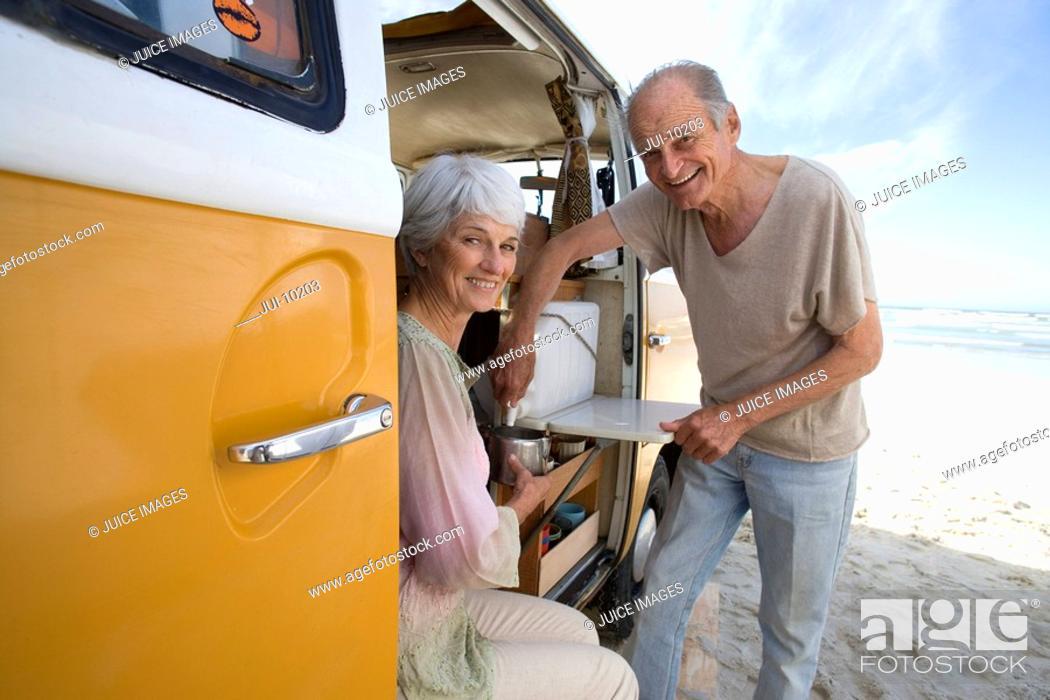 Stock Photo: Senior couple making tea in camper van on beach, smiling, portrait, side view.