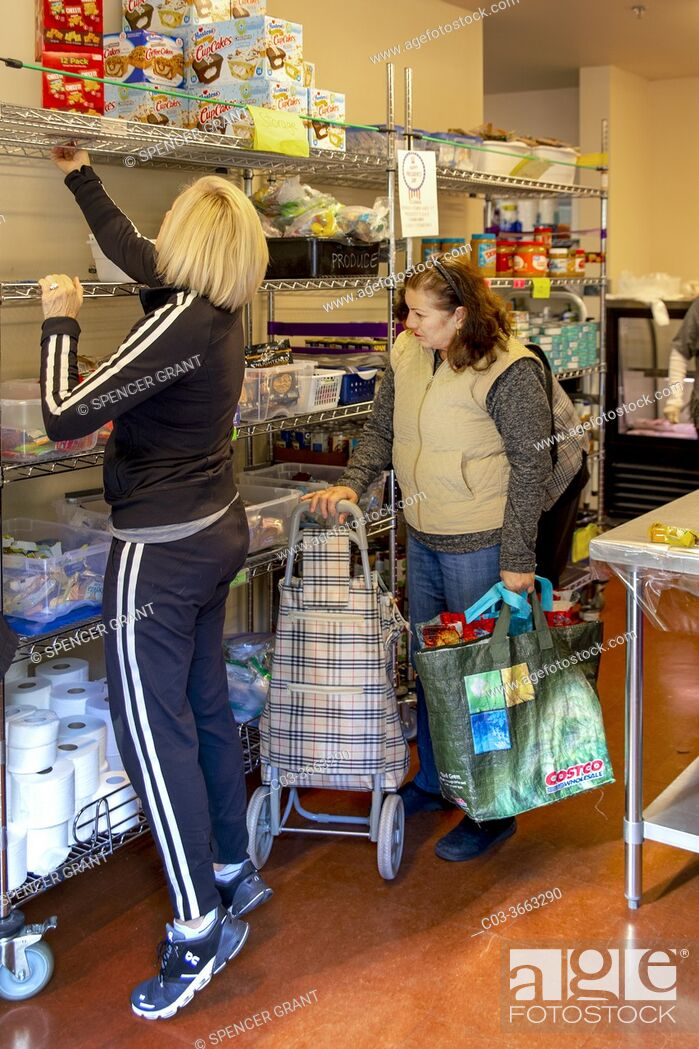 Stock Photo: A Hispanic client at the charity food pantry of a Southern California Catholic church greets is assisted by a church volunteer.