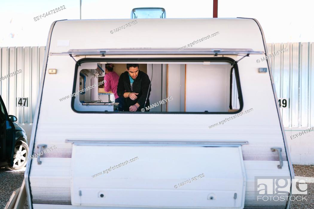 Stock Photo: Young couple painting and restoring caravan.