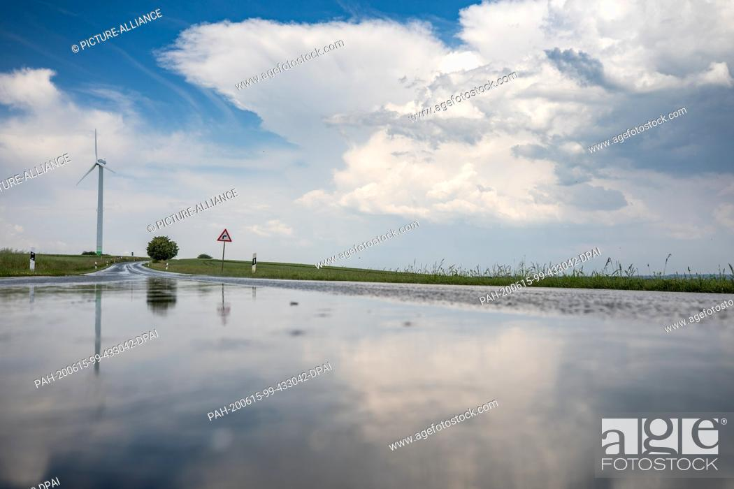 Stock Photo: 13 June 2020, Saxony, Waldenburg: The landscape is reflected in the wet country road after a rain shower. Photo: Jan Woitas/dpa-Zentralbild/ZB.