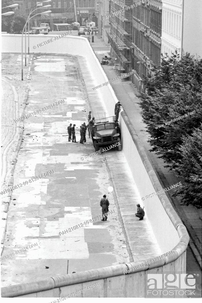 Stock Photo: 08 August 1985, Berlin: GDR border guards paint the wall at Sebastianstraße in the Kreuzberg district with white paint. On the right.