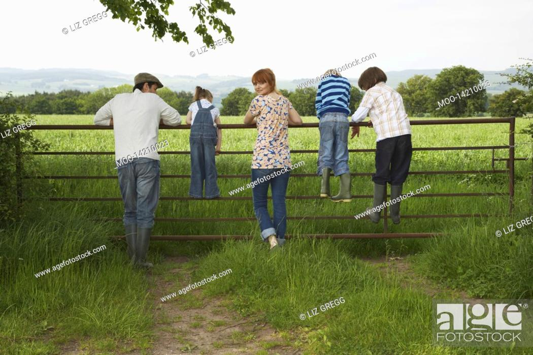 Stock Photo: Parents with three children 5-9 standing on fence in countryside.
