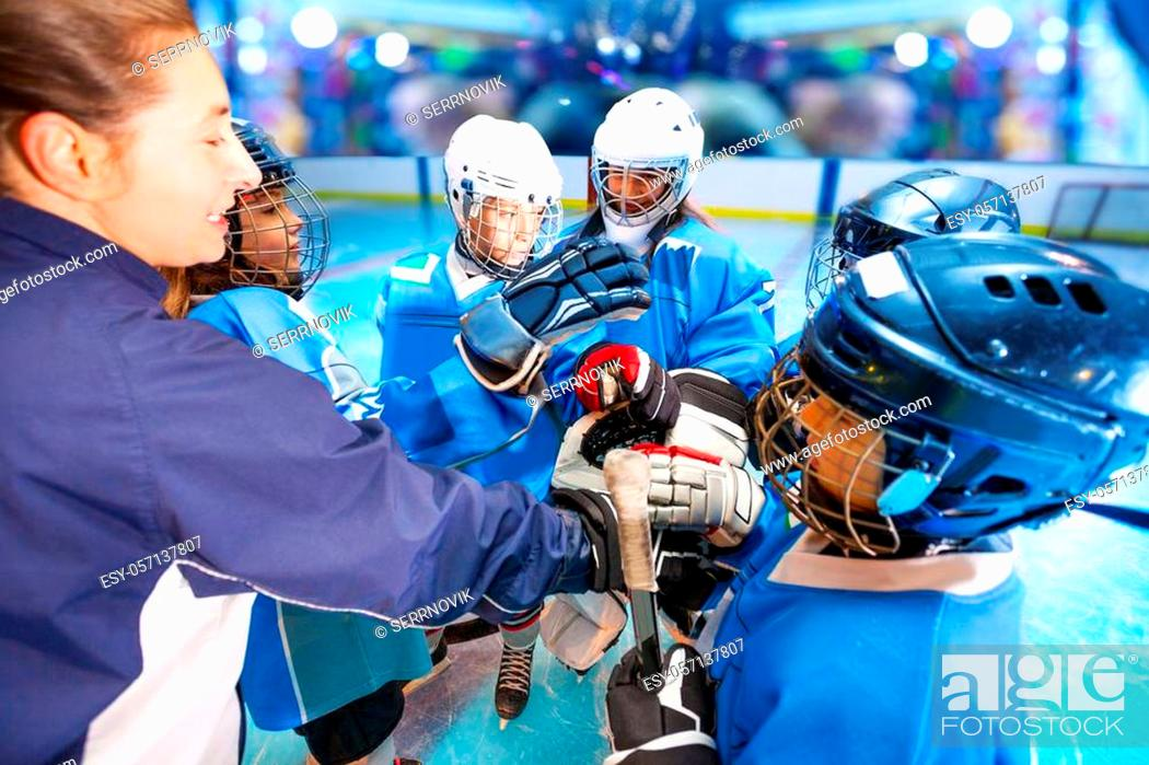 Stock Photo: Close-up portrait of female coach and ice hockey team putting hands in huddle before the game, in junior league.