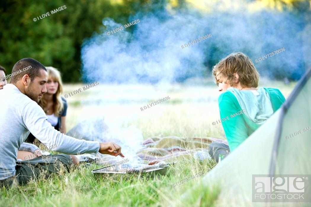 Stock Photo: A group of young friends having a barbecue outdoors next to a tent.