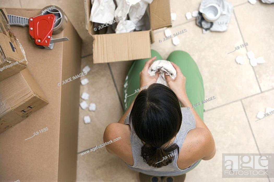 Stock Photo: Woman sitting on floor, packing box, wrapping bowl in paper, overhead view.