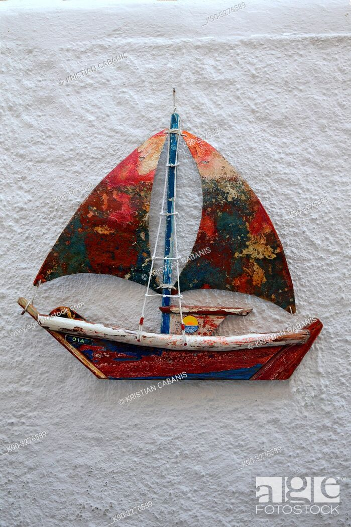 Stock Photo: Toy sailboat hanging on a white wall, Oia, Santorin, Greece, Europe.