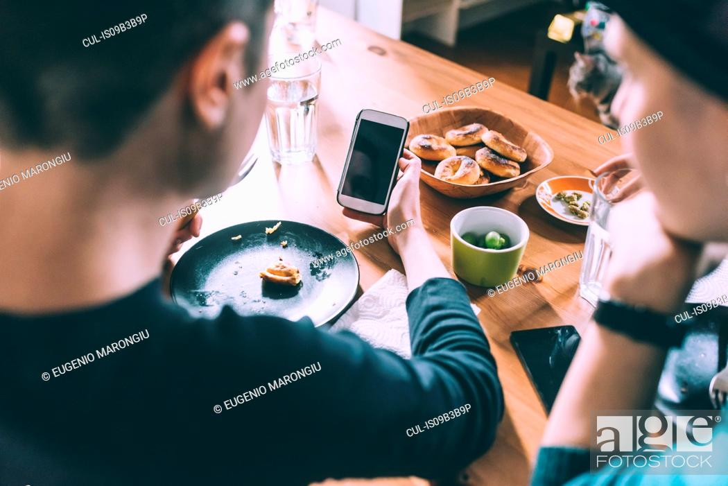 Stock Photo: Over shoulder view of two young female friends reading smartphone texts at kitchen table.