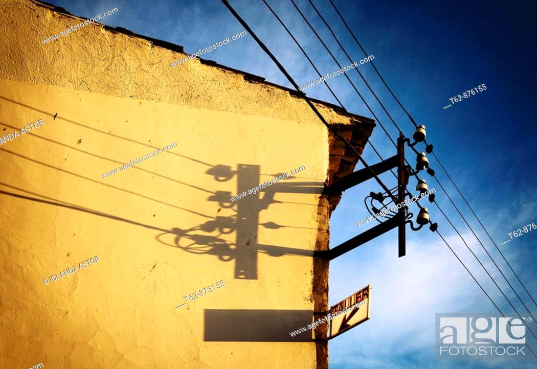 Stock Photo: Electricity pole in a yellow wall illuminated by the sun in the evening  Spain.