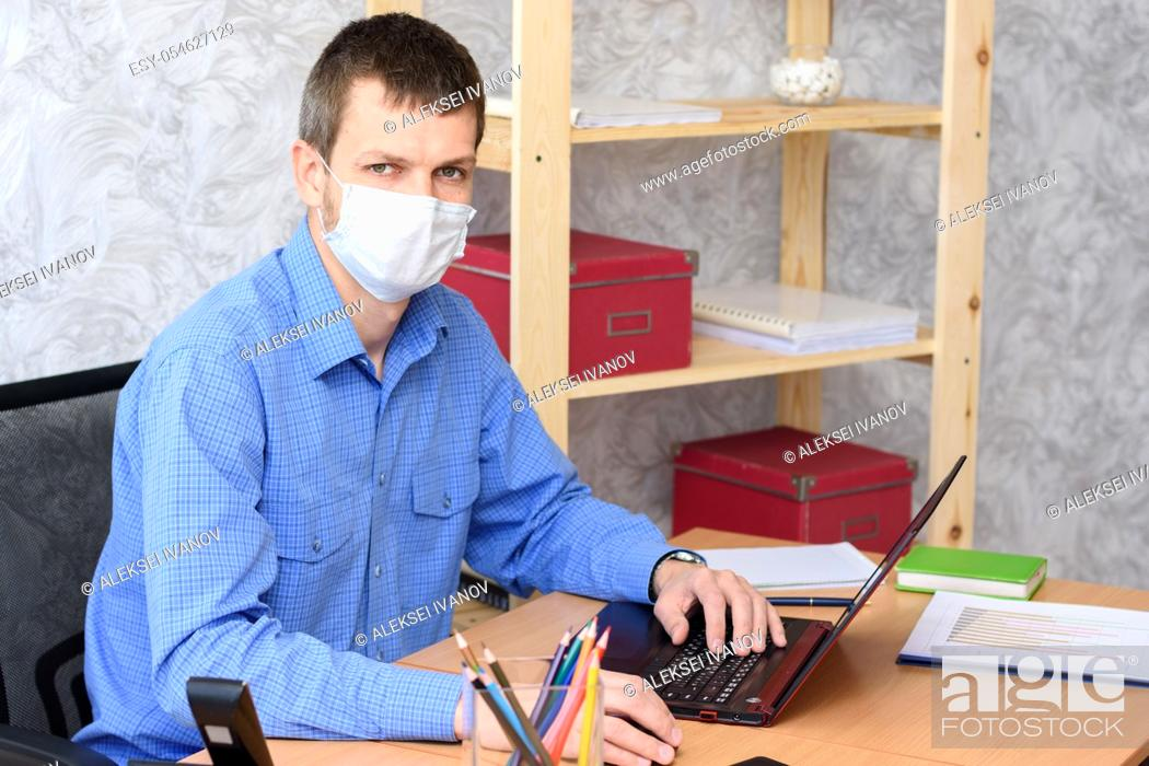 Stock Photo: Portrait of an office worker in a medical mask at a desk.