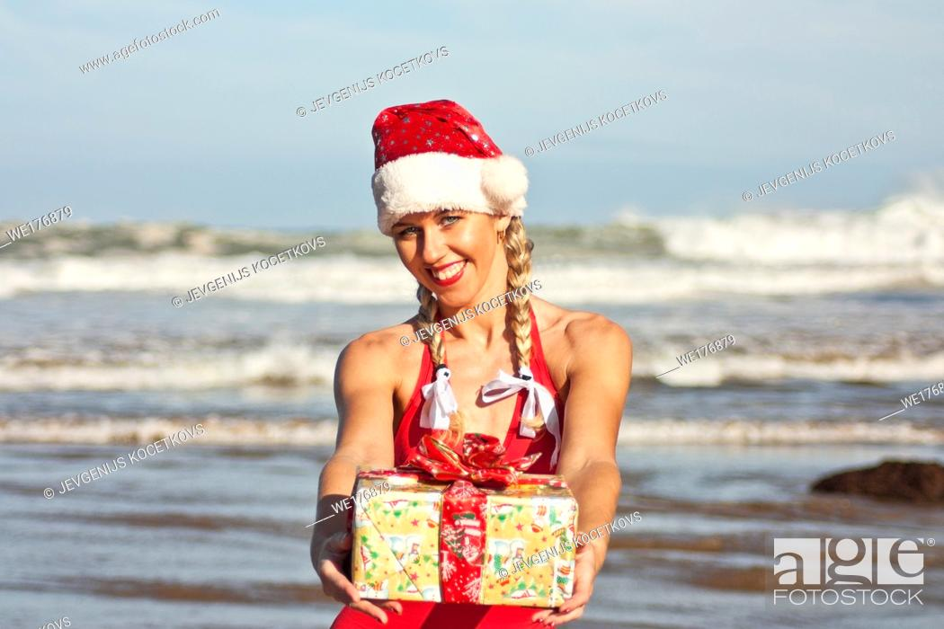 Stock Photo: Santa girl in Santa hat with Christmas gift on the beach.