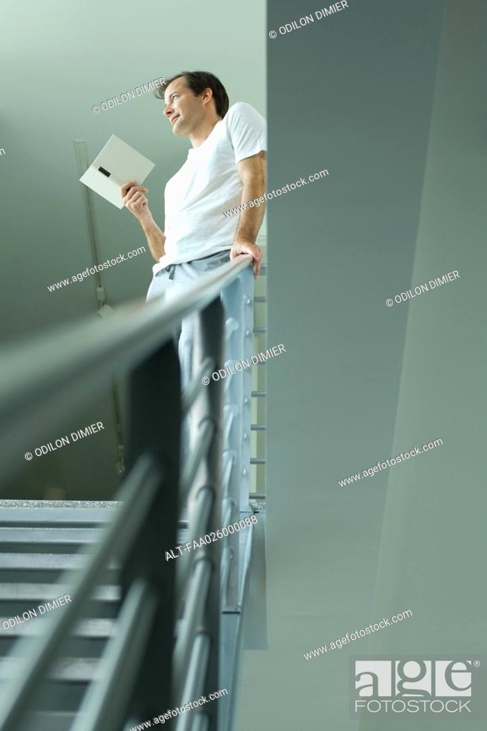 Stock Photo: Man standing at top of staircase, holding book, looking away.
