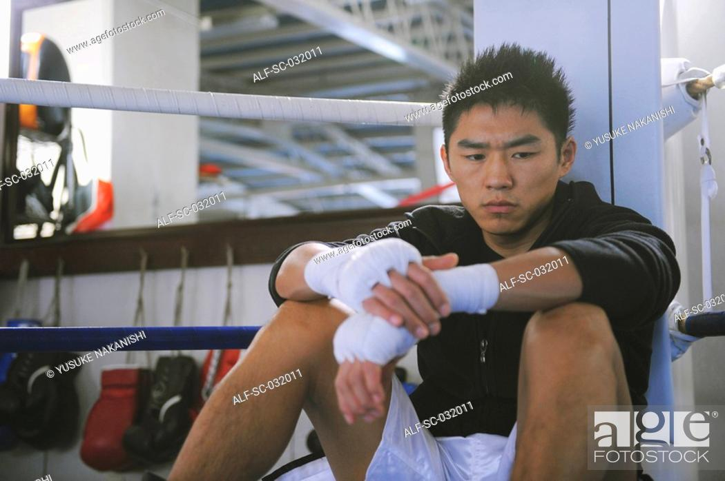 Stock Photo: Japanese boxer sitting in Boxing ring.