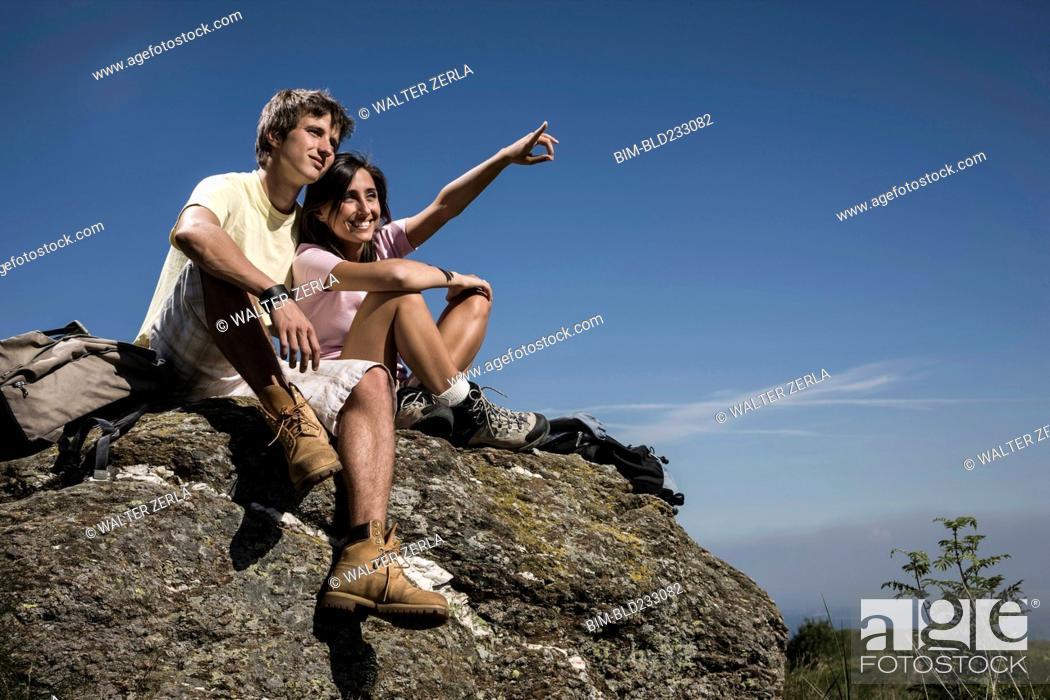 Stock Photo: Smiling couple sitting on rock.