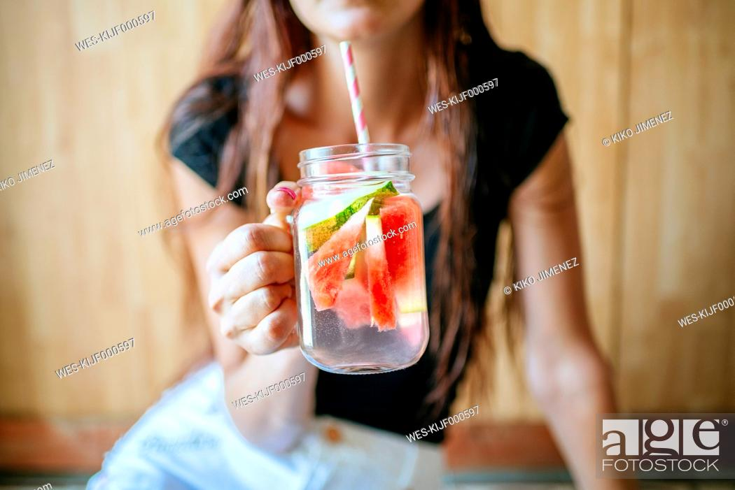 Stock Photo: Close-up of woman holding a glass of watermelon.