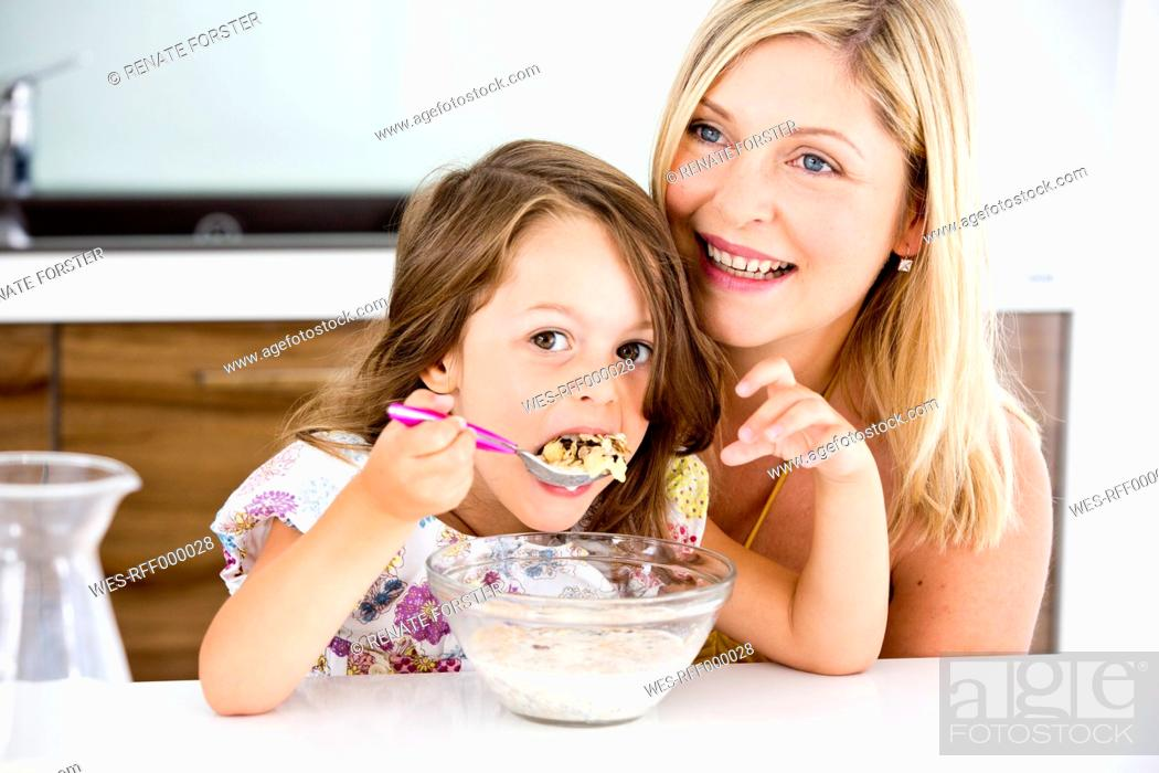 Stock Photo: Germany, Daughter eating muesli in kitchen.
