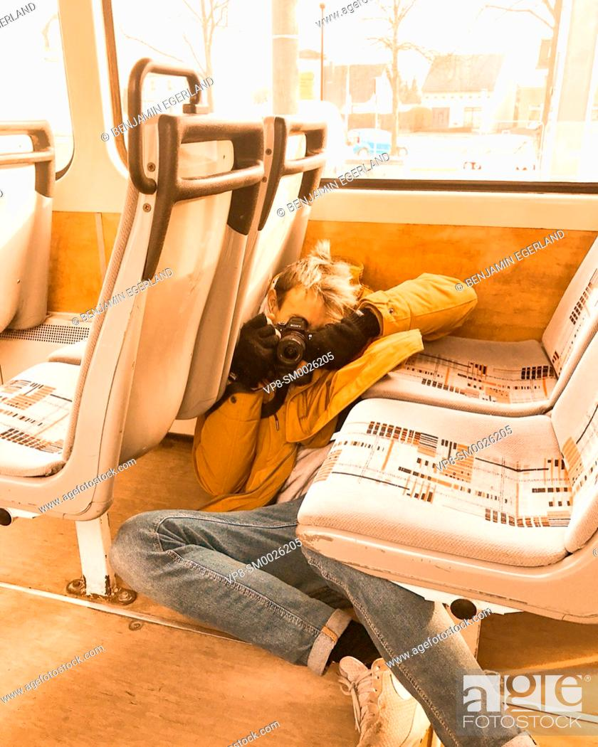 Imagen: models view of playful photographer laying on floor between seats in city tram, public transport, taking photographs, in Cottbus, Germany.