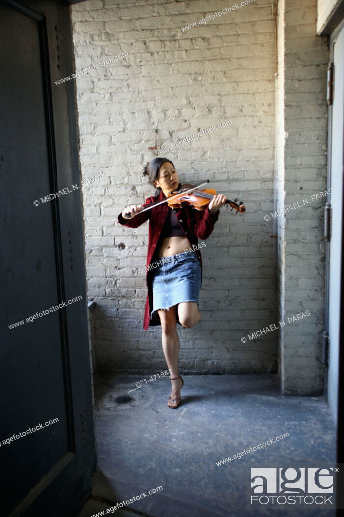 Stock Photo: Sexy asian woman playing violin in stairwell.