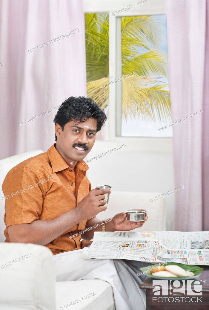 Stock Photo: South Indian man reading a newspaper and having breakfast.