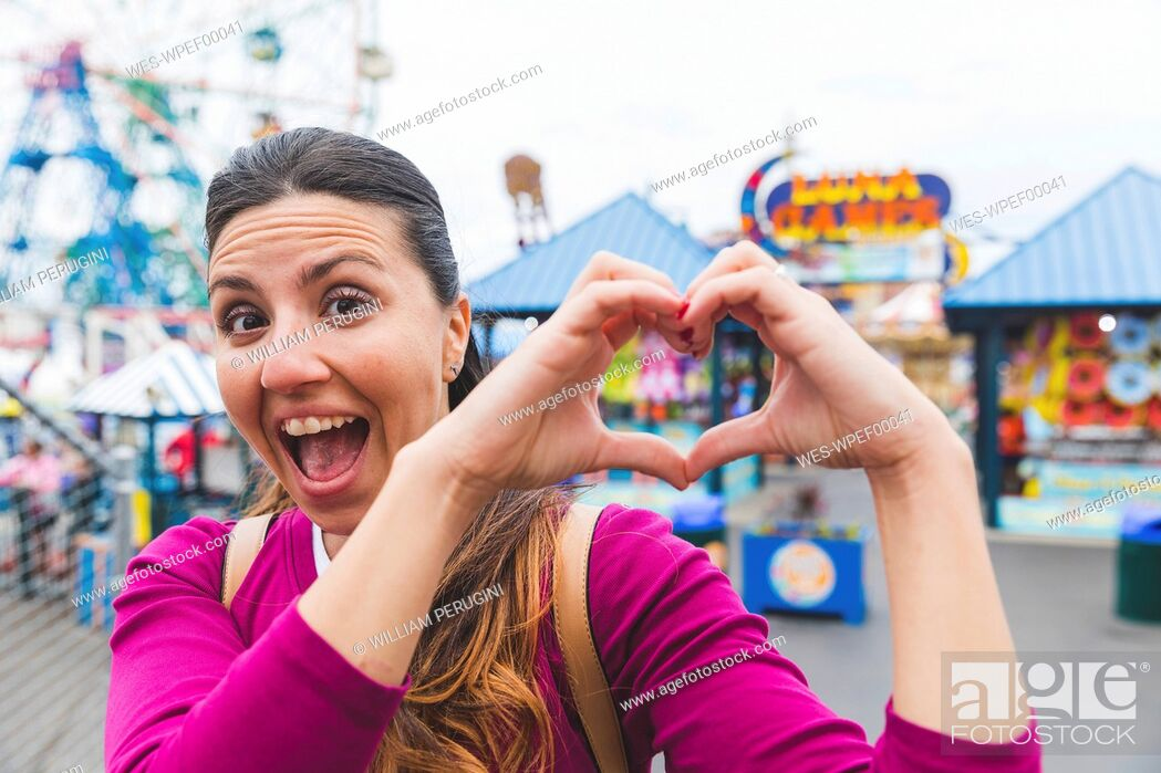 Stock Photo: USA, New York, portrait of excited woman at Coney Island shaping heart with her hands.