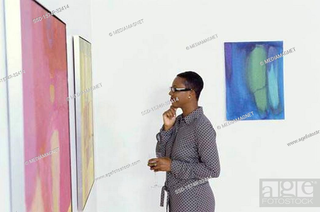 Imagen: Young woman holding a glass looking at paintings on a wall.