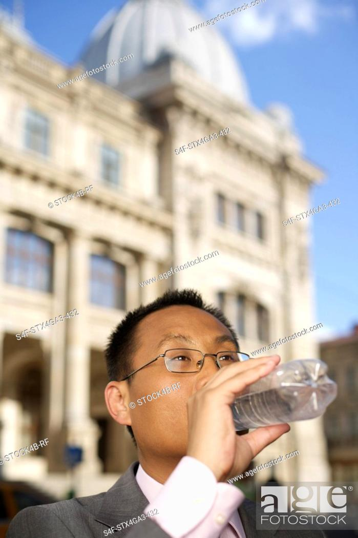 Stock Photo: Businessman drinking water out of a plastic bottle.