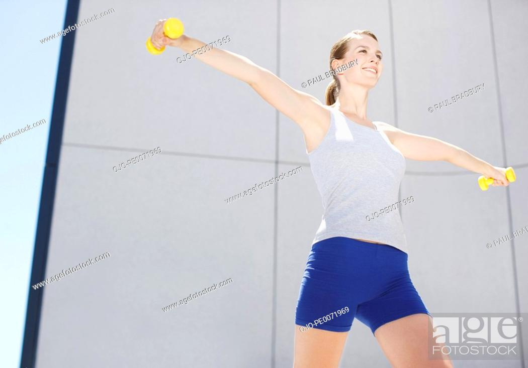 Stock Photo: Woman using hand weights outdoors.
