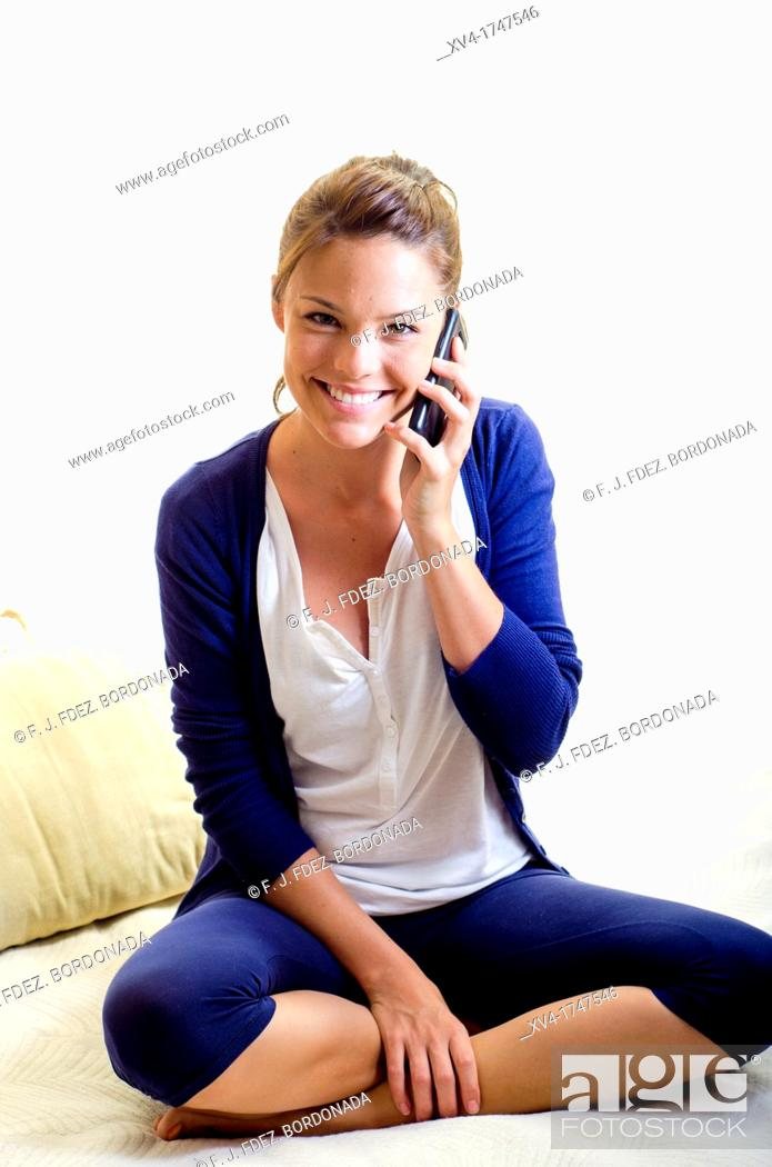 Stock Photo: Pretty girl talk with mobile phone in the bedroom.