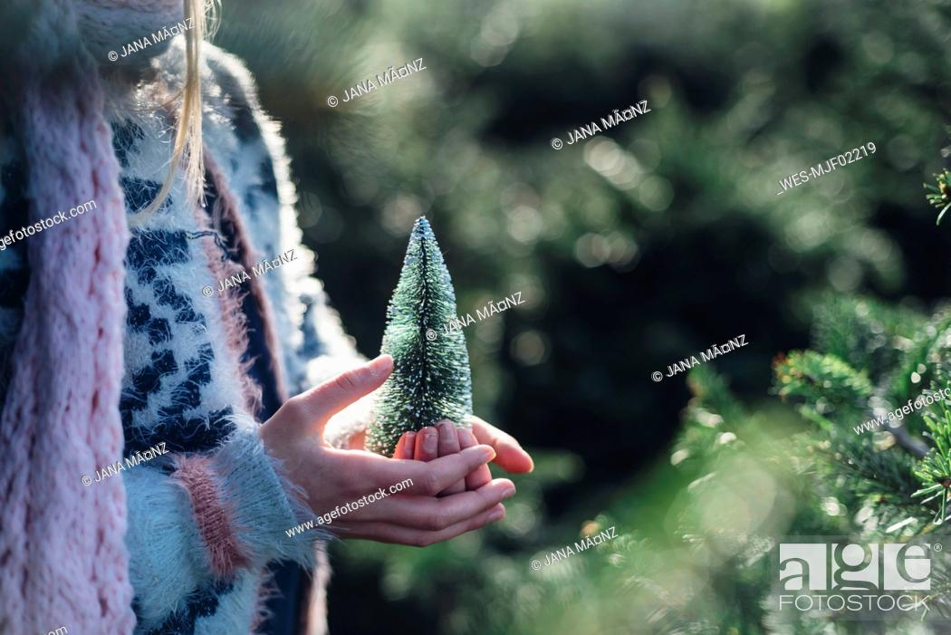 Stock Photo: Little girl holding a toy Christmas tree, close up.