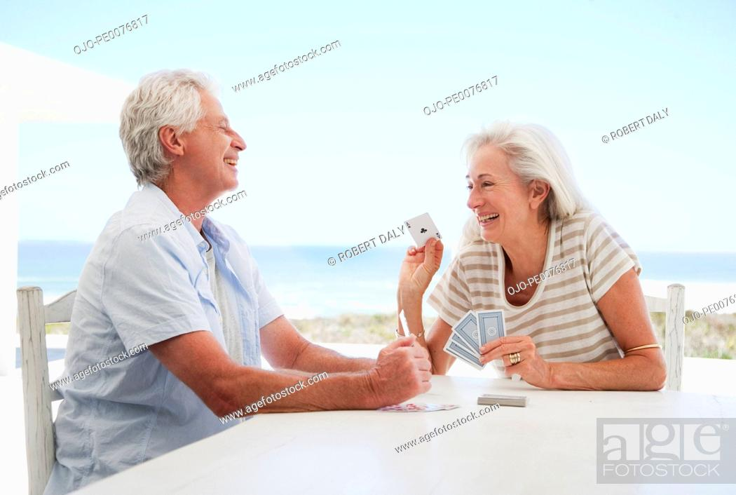 Stock Photo: Couple playing cards on patio at beach.