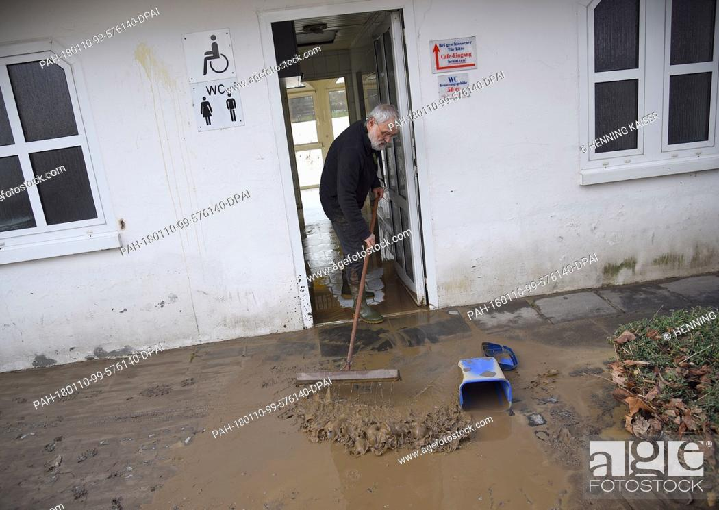 Stock Photo: A man cleaning up a cafe along the Rhine Promenade, which was left covered in mood by the high waters of the Rhine, in Koenigswinter, Germany, 10 January 2018.