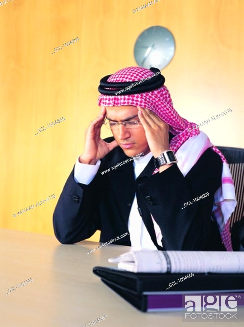 Stock Photo: Saudi Arabian businessman holding his head.