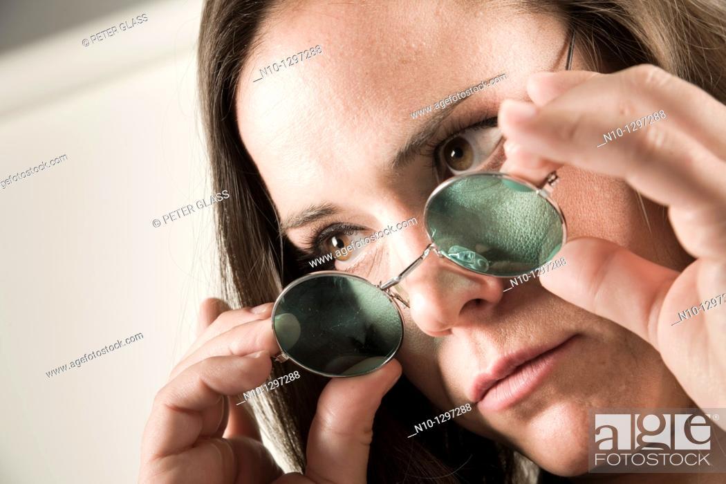 Stock Photo: Young woman wearing sunglasses.
