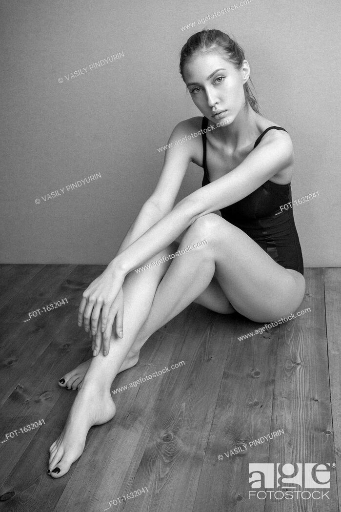 Stock Photo: Portrait of confident woman wearing leotard sitting on hardwood floor against wall.