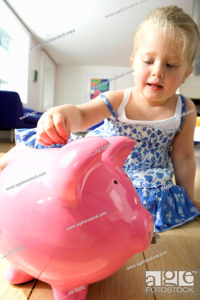Stock Photo: Girl 2-4 putting coin in piggy bank, low angle view.
