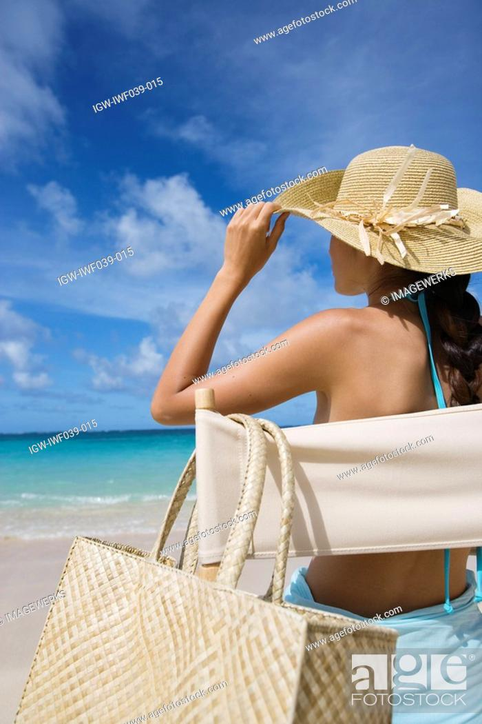 Stock Photo: A woman sitting on chair on beach.