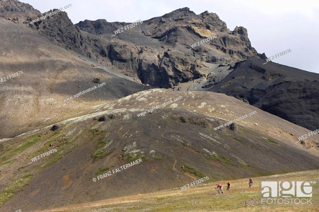 Stock Photo: Iceland, Men mountain biking in hilly landscape.