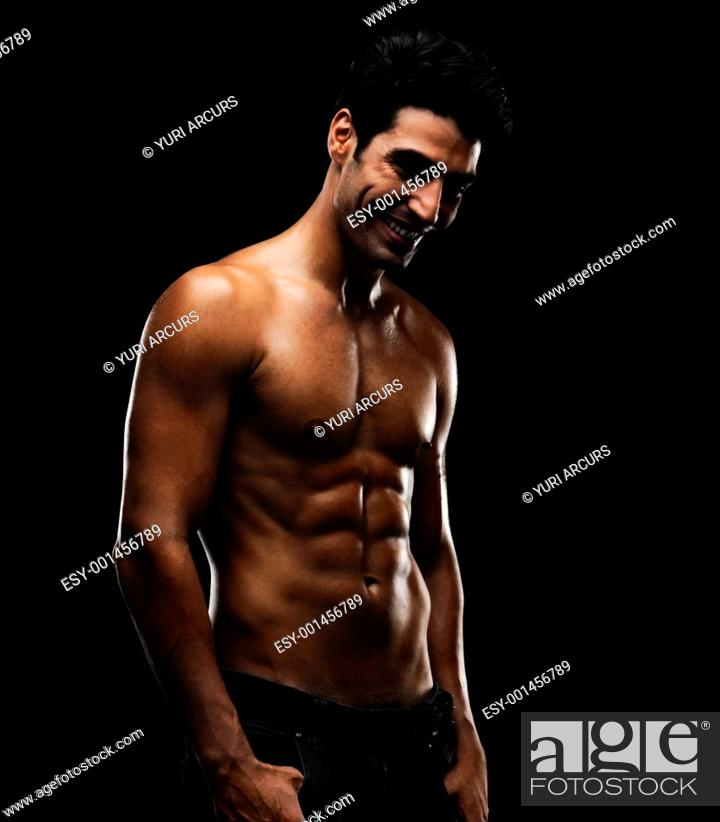 Stock Photo: Sexy muscular man smiling over a happy thought against black background.