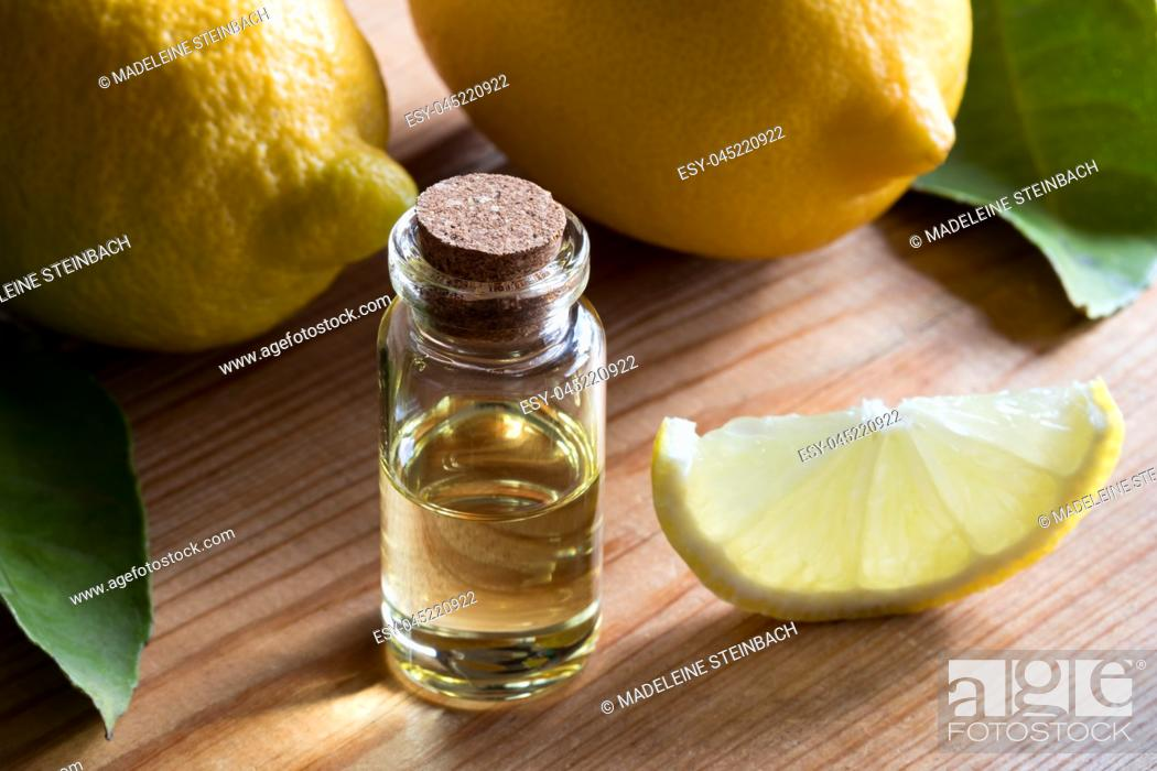 Stock Photo: A bottle of lemon essential oil on a wooden table, with lemons in the background.