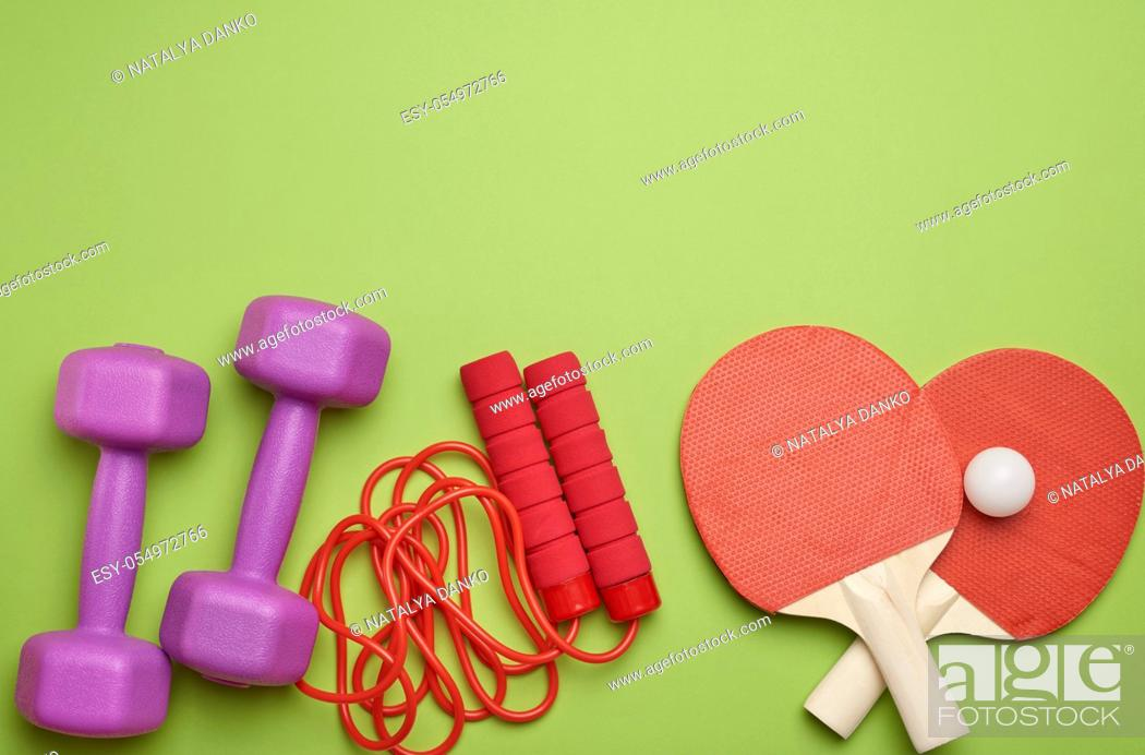 Stock Photo: sneakers, jump rope and wooden rackets for table tennis on a green background, place for an inscription, flat lay.