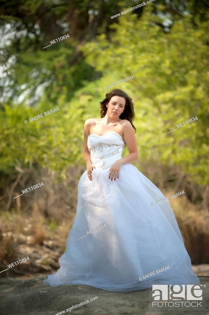 Stock Photo: Trash the dress - young bride getting into a river.