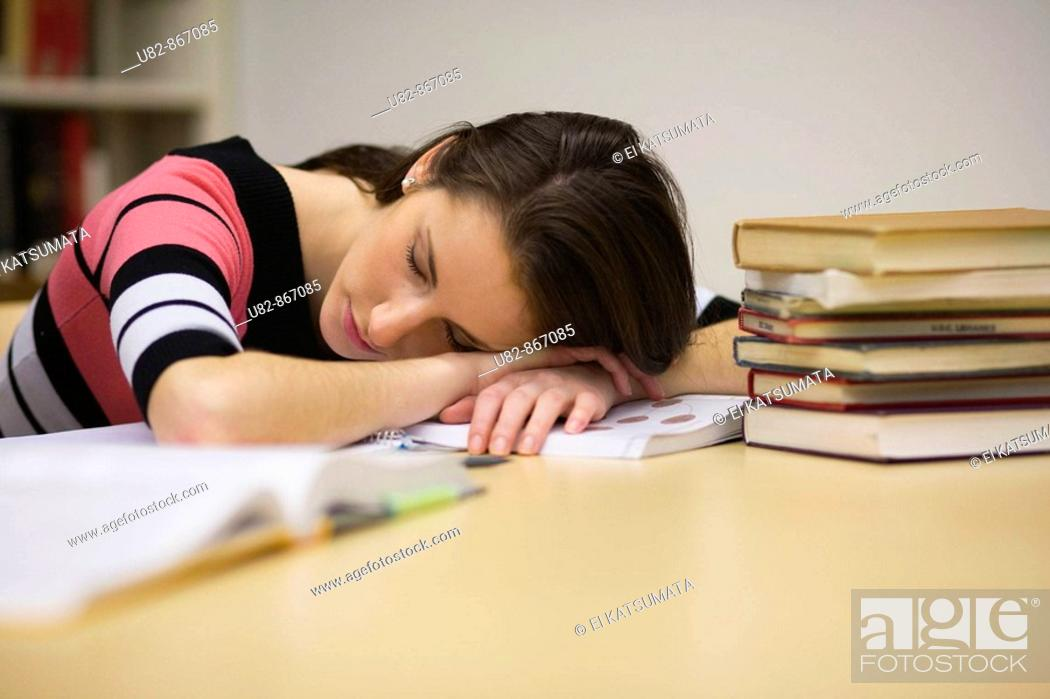 Stock Photo: A young woman sleeping in a library.
