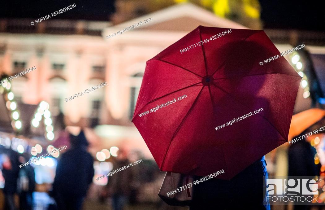 Stock Photo: A woman walks with an umbrella over the grounds of the Christmas market in front of Charlottenburg Palace in Berlin, Germany, 27 November 2017.