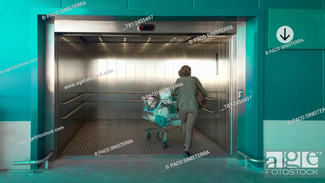 Stock Photo: Woman with shopping cart entering an elevator, Barcelona, Spain.