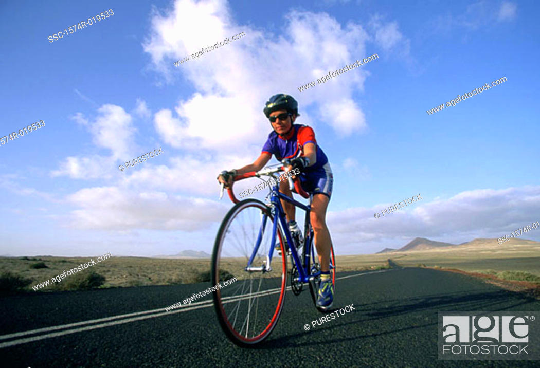 Stock Photo: Woman riding bicycle down road.