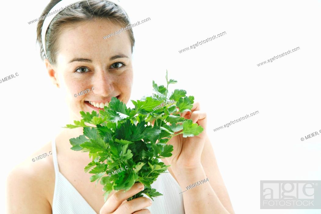 Imagen: young woman holding a bunch of lovage in her hands and is taking a smell on it.