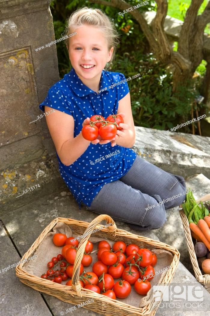 Stock Photo: Girl 9-11 with basket of tomatoes, smiling, portrait.